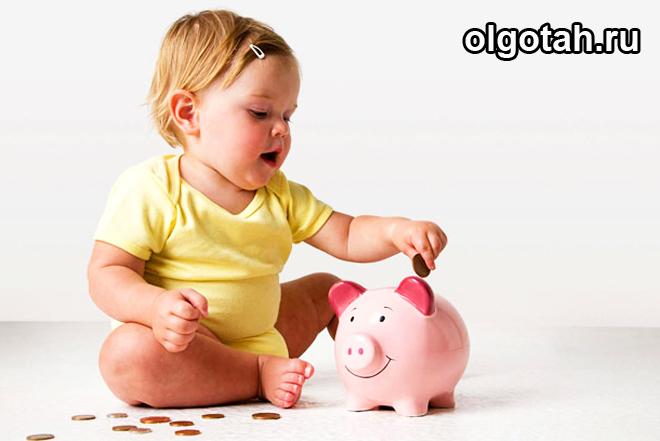 Маленький ребенок кидает монетку в копилку