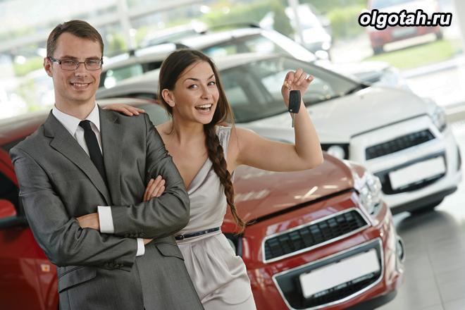 Счастливая девушка держит ключи от только что купленного автомобиля