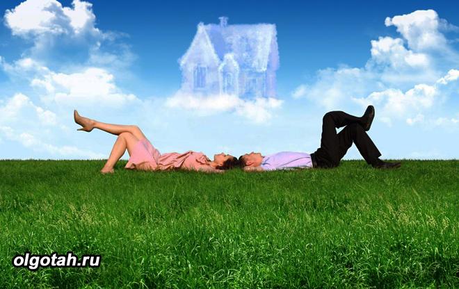 Молодая пара лежит на лужайке и мечтает о своем новом доме