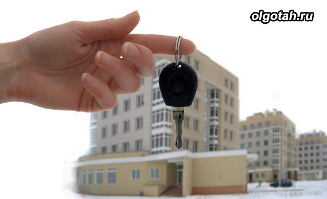Человек держит в руке ключ от квартиры