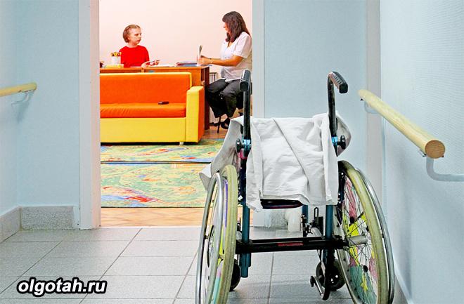 Ребенок на приеме у врача, в коридоре инвалидное кресло