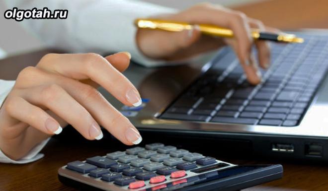 Девушка сидит за компьютером и считает на калькуляторе