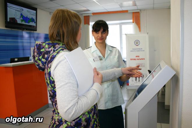 Налоговый инспектор помогает пользоваться терминалом плательщику