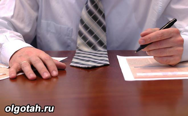 Мужчина в галстуке заполняет документы за столом