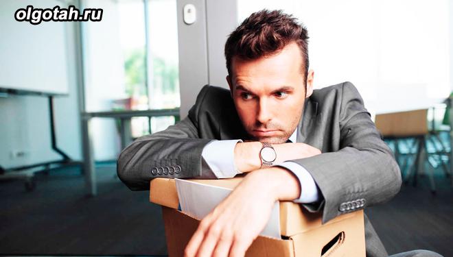 Расстроенный мужчина сидит с упакованной коробкой