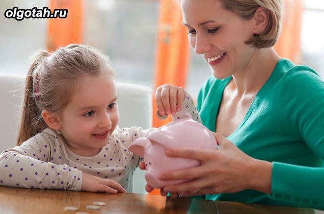 Девочка кладет монетку в копилку, мама рядом