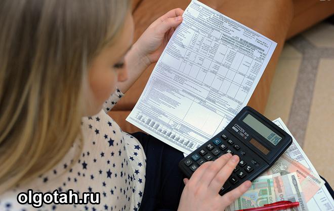 Девушка считает на калькуляторе, в руке держит платежку