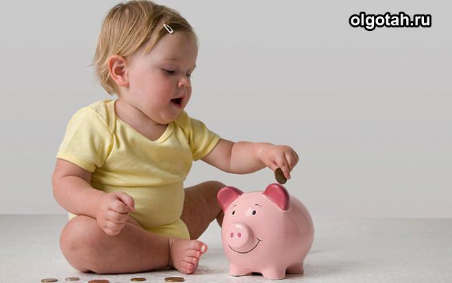 Маленькая девочка кидает монетку в копилку