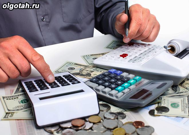 Мужчина считает деньги на калькуляторе