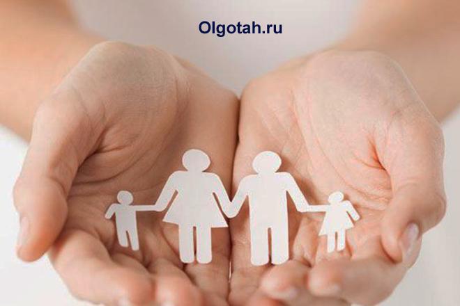 Силуэт семьи из бумаги в руках человека