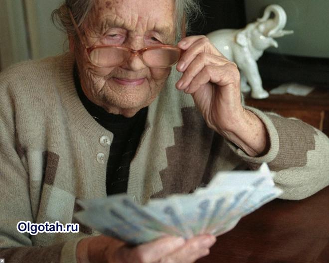 Пенсионерка держит деньги в руках