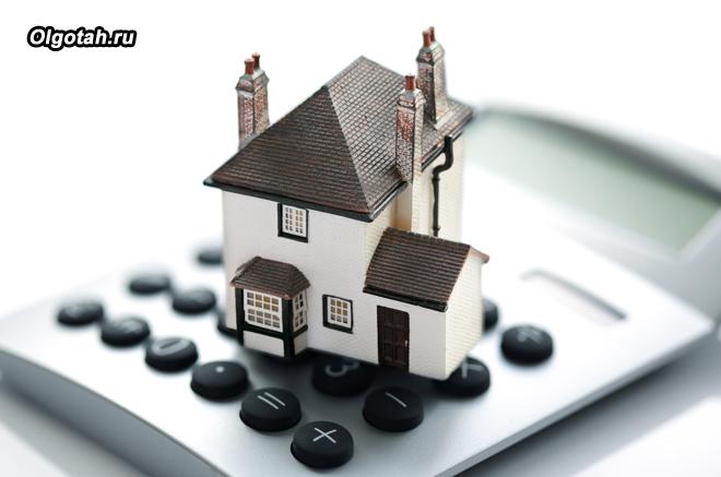 Игрушечный домик стоит на калькуляторе