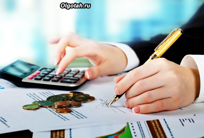 Бизнесмен ведет расчеты на калькуляторе