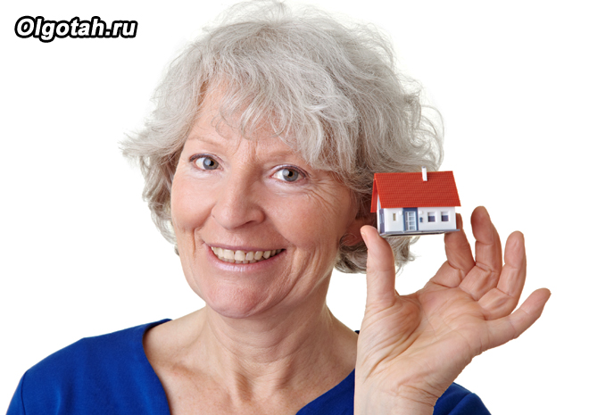 Пенсионерка держит игрушечный домик