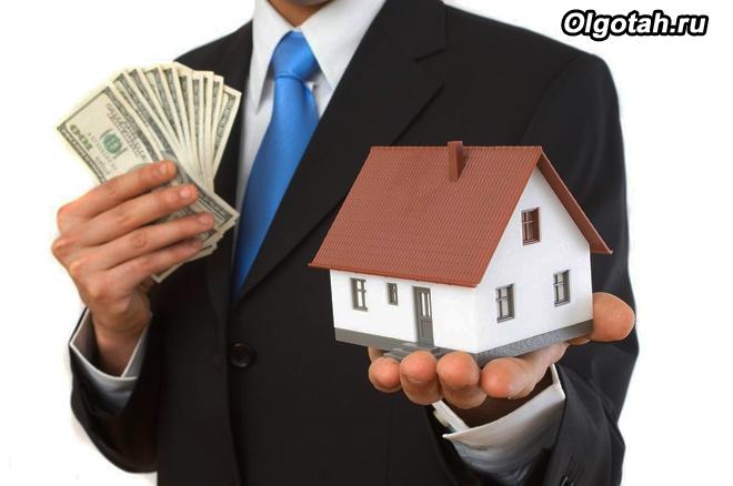 Мужчина в деловом костюме держит игрушечный домик и деньги