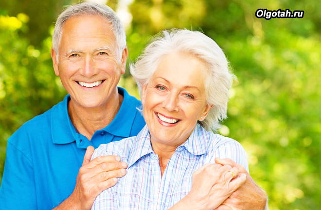 Счастливая пожилая пара на фоне зелени