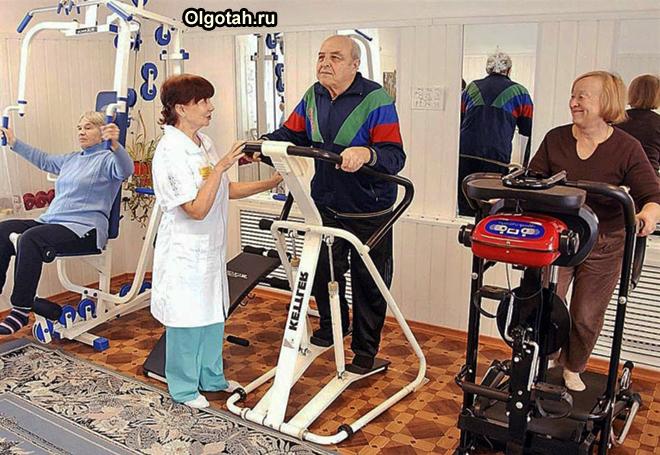 Пенсионеры занимаются на тренажерах под присмотром медика