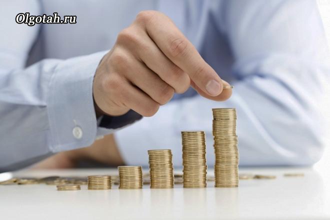 Мужчина в рубашке выкладывает монеты по возрастанию