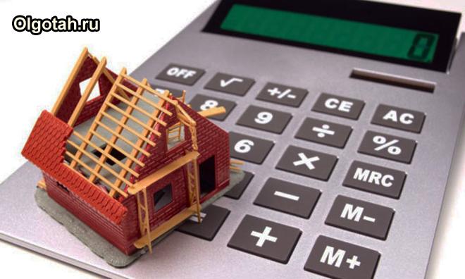 Игрушечный недостроенный домик стоит на калькуляторе