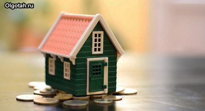 Игрушечный домик стоит на монетах