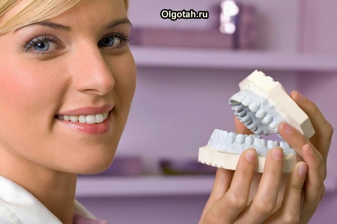Стоматолог держит в руках зубной протез