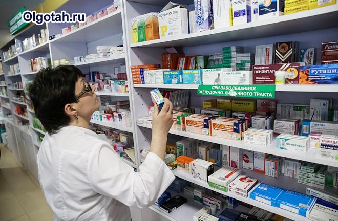 Фармацевт ищет лекарство на полке