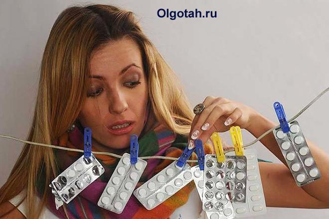 Девушка смотрит таблетки, которые висят на бельевой веревке