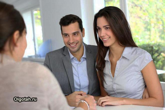 Молодая пара общается с банковским работником