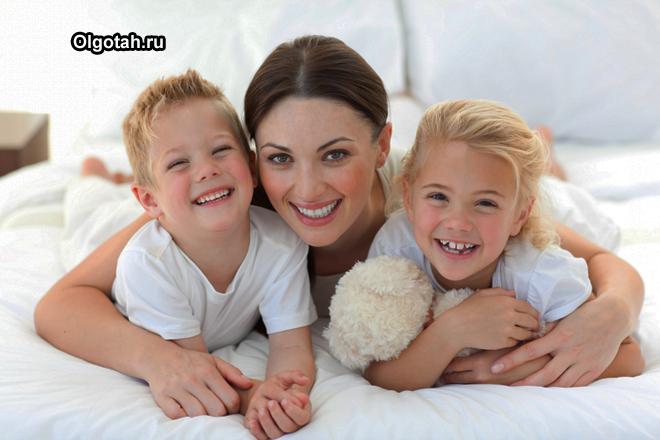 Мама обнимает дочку и сына