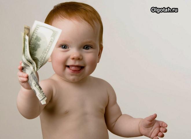 Маленький ребенок держит в руке деньги