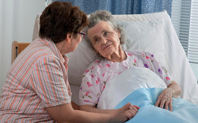 Женщина ухаживает за пенсионеркой в больнице