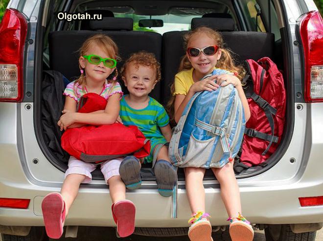 Дети сидят в багажнике машины