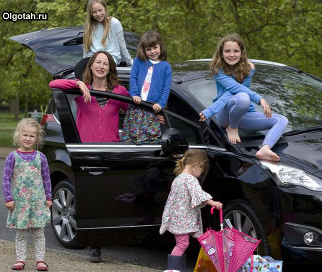 Многодетная мама с детьми стоит около машины