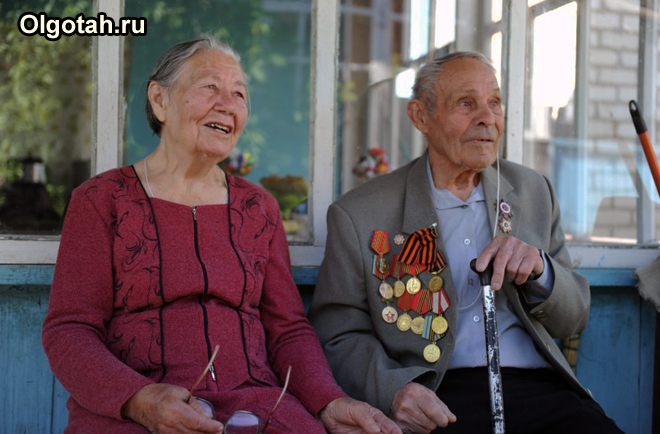 Пожилая пара сидит на лавочке