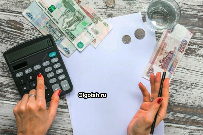 Девушка считает на калькуляторе денежные средства