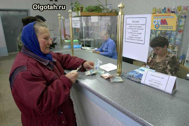 Пенсионерка стоит на приеме в окно