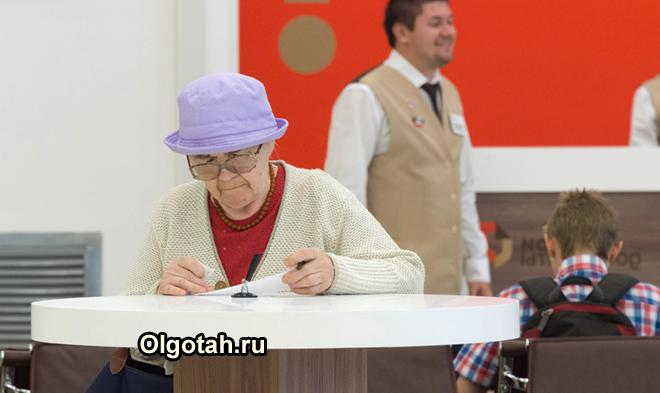 Пенсионерка заполняет заявление за столом