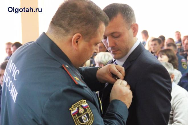 Сотрудник МЧС награждает гражданина медалью