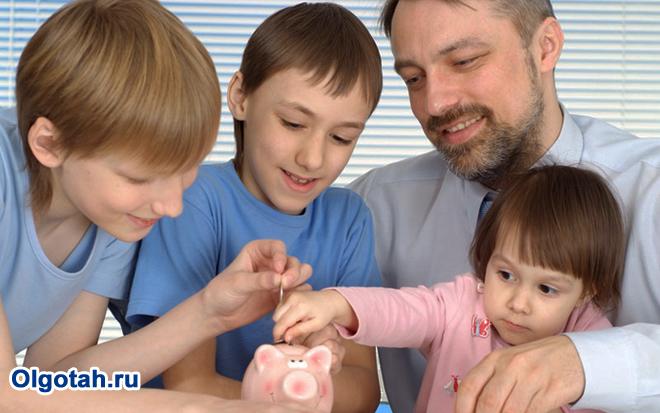 Папа с детьми кладут монетки в копилку