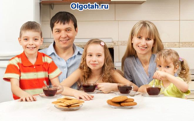 Семья пьет вместе чай на кухне