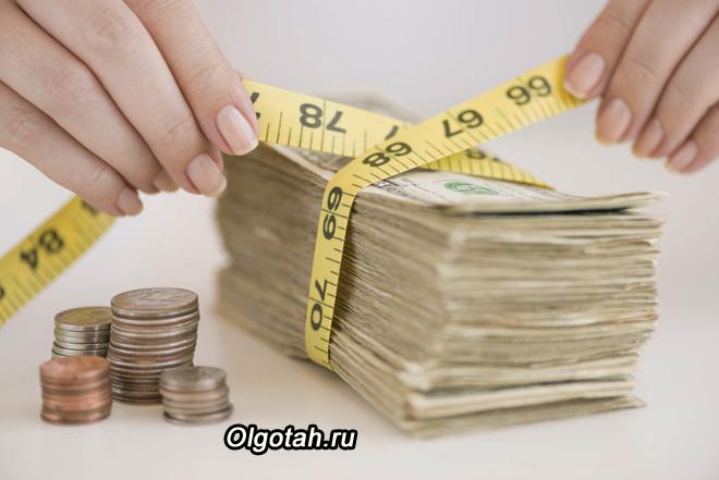 Пачку денежных купюр измеряют лентой
