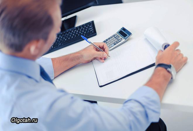 Бизнесмен с записной книжкой и калькулятором