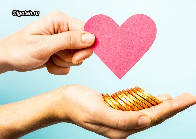 Девушка держит в руках бумажное сердечко и монеты