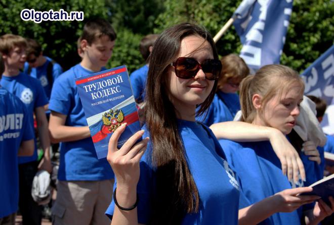 Девушка держит в руке Трудовой кодекс РФ