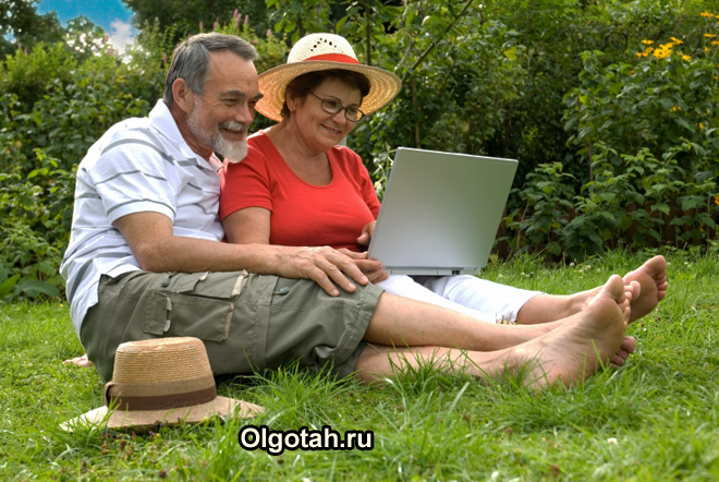 Муж с женой сидят на лужайке и смотрят в ноутбук
