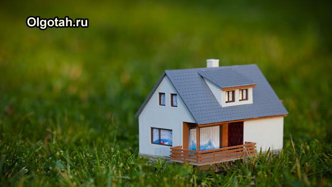 Игрушечный дачный домик стоит в поле