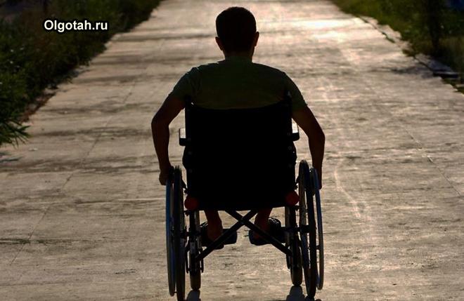 Мужчина в инвалидной коляске едет по аллее