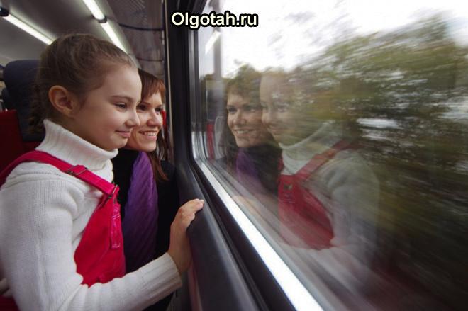 Школьница с мамой смотрят в окно в поезде