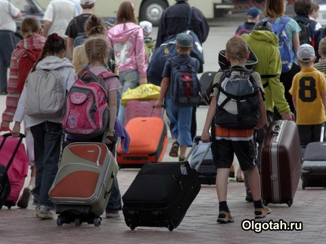 Школьники идут по платформе с чемоданами