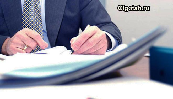 Офисный работник оформляет документацию